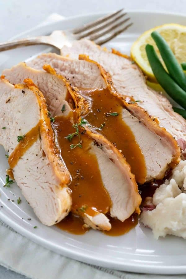 slices of turkey breast on a plate with gravy on top