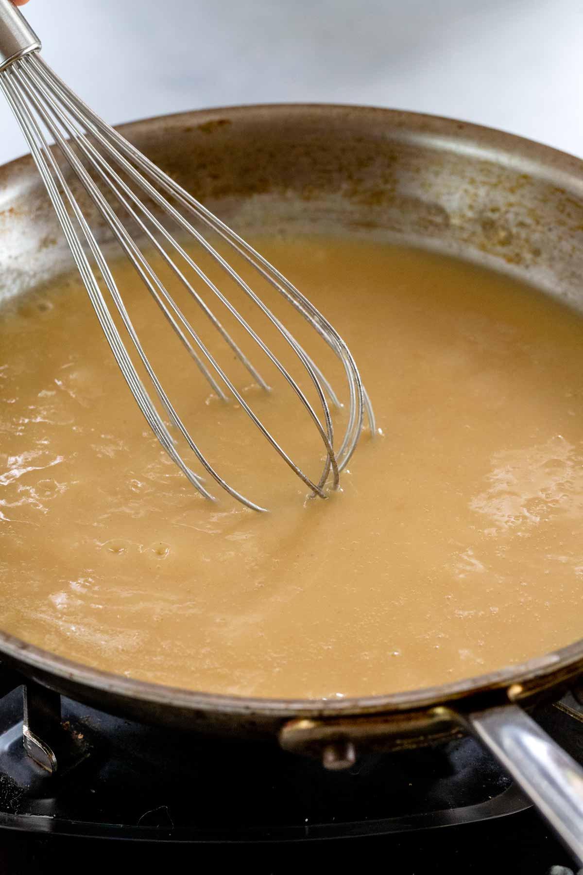 whisk stirring a pan full of gravy