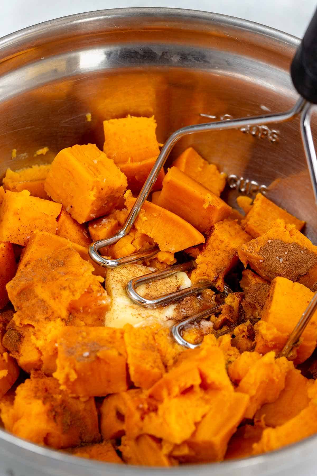 using a potato masher in a bowl with cubes of sweet potatoes