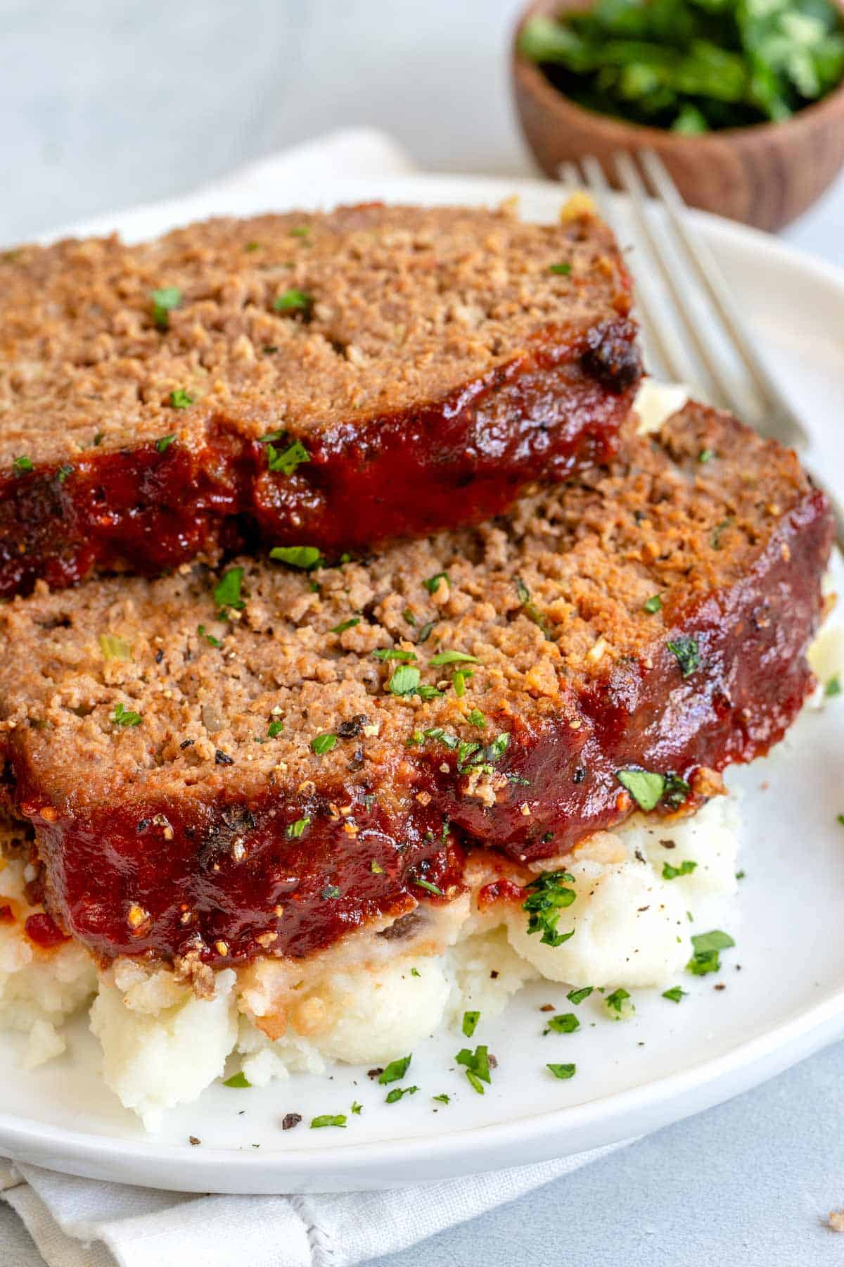 two slices of meatloaf on a dinner plate served with mashed potatoes