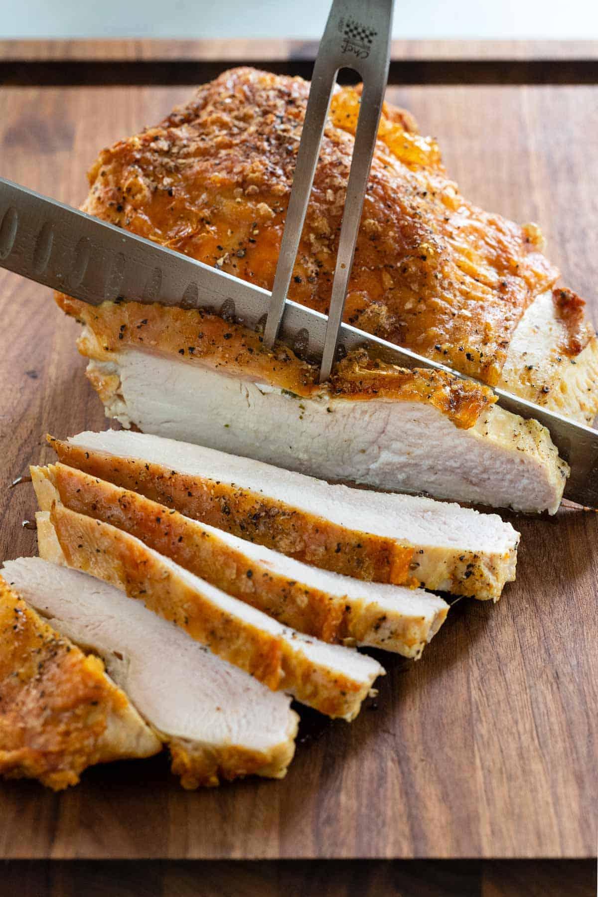 roast turkey breast being sliced with a knife on a cutting board