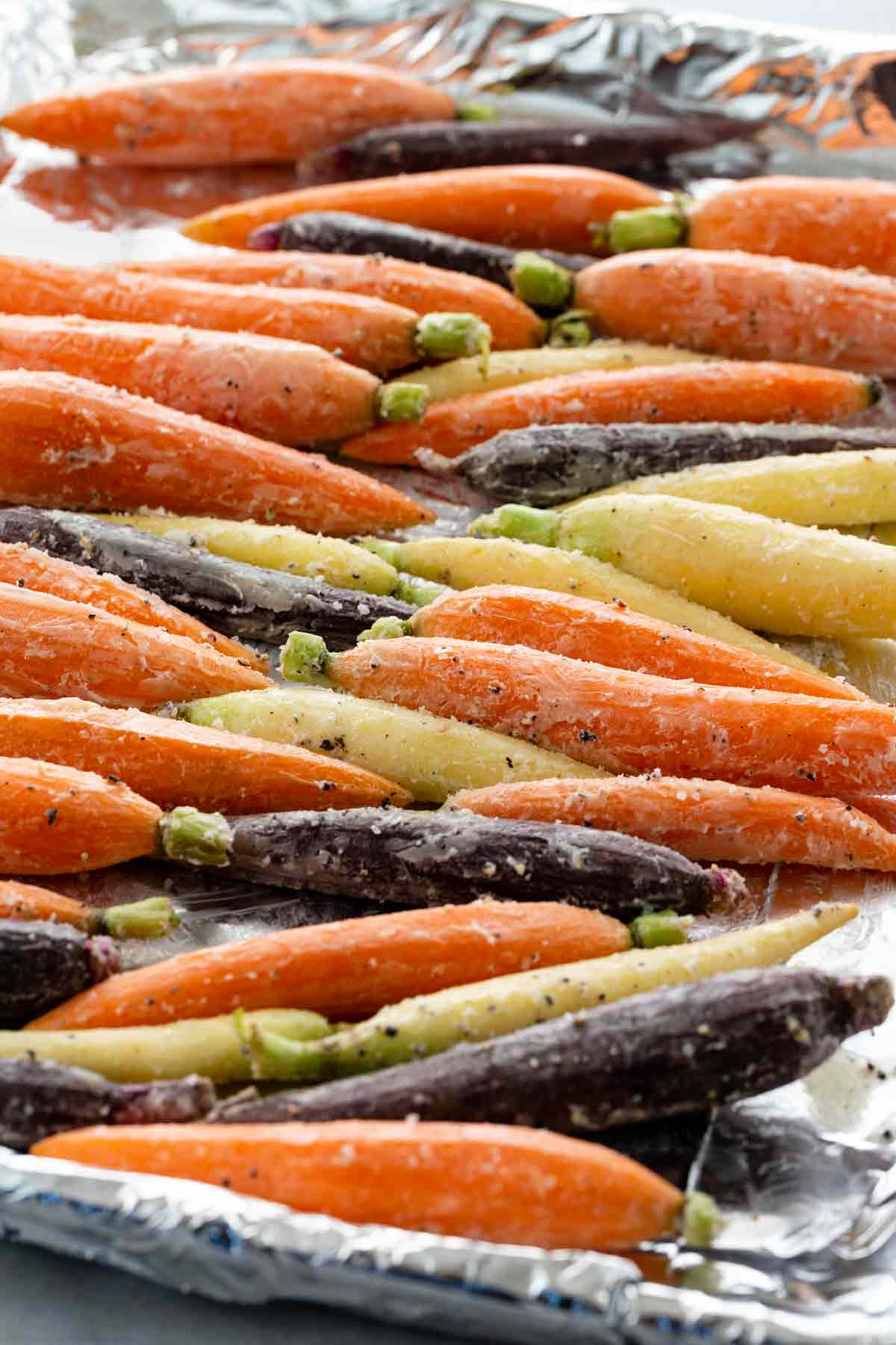 seasoned carrots lined up on a foil-lined baking sheet