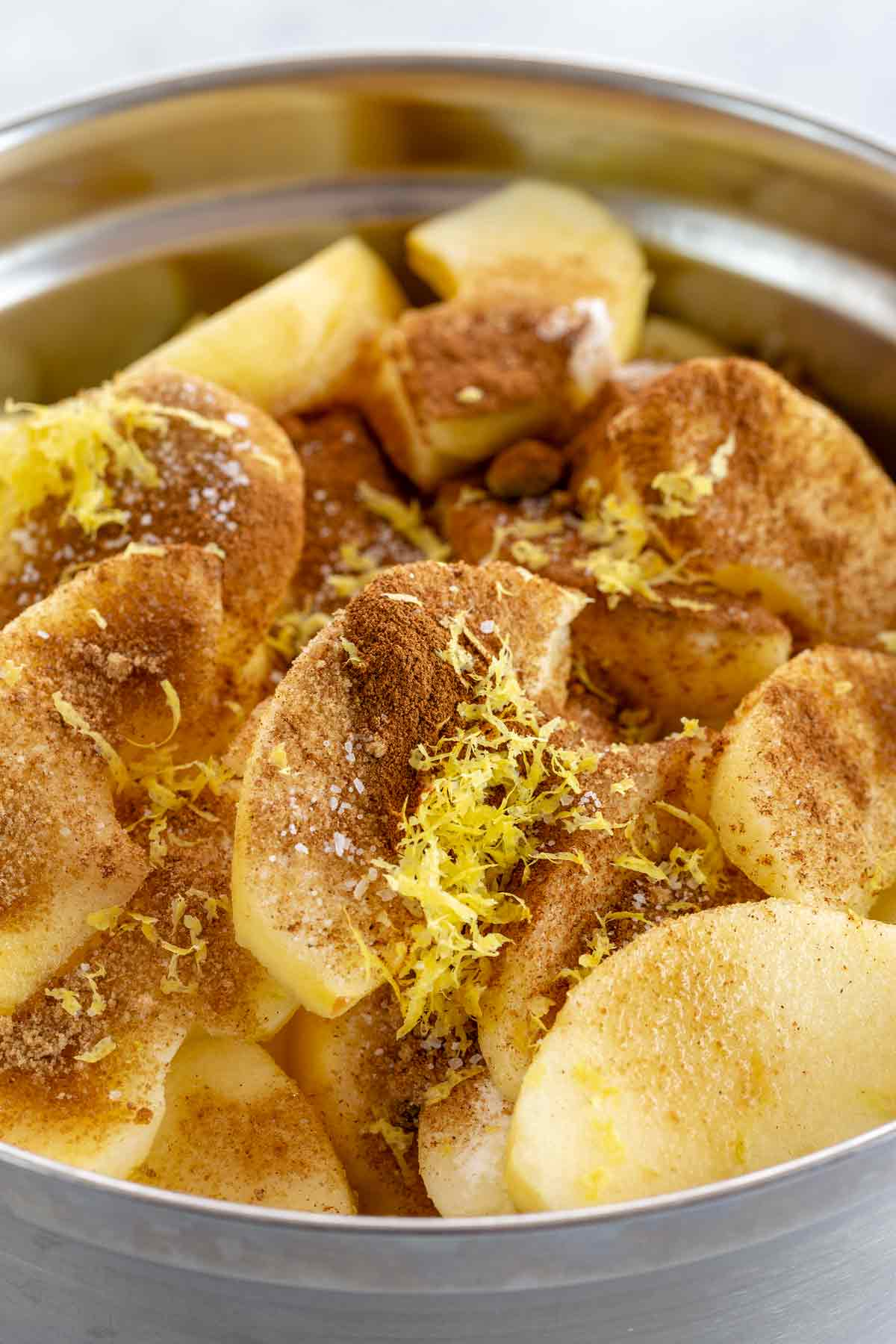 Slices of Honeycrisp apples in a bowl with cinnamon spices and lemon zest on top
