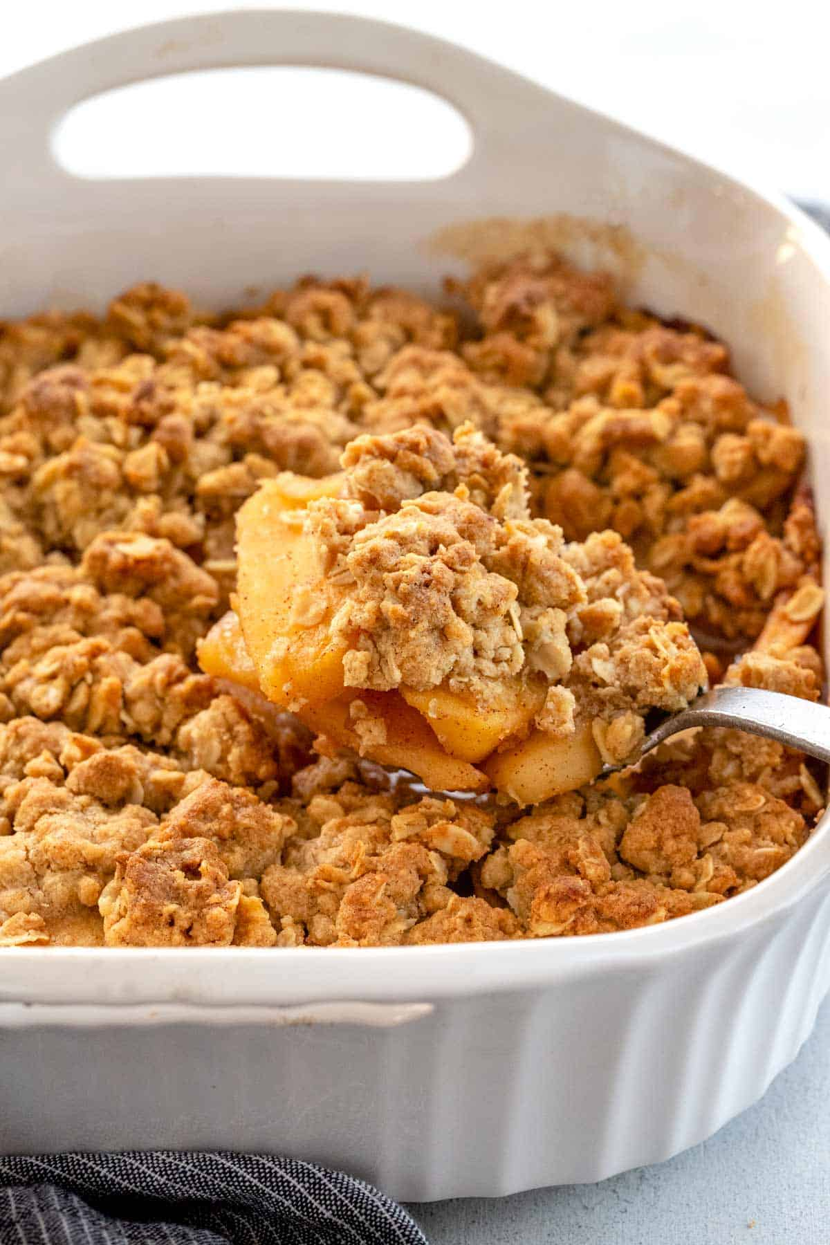Apple crisp from the oven with golden crunchy topping in a casserole dish