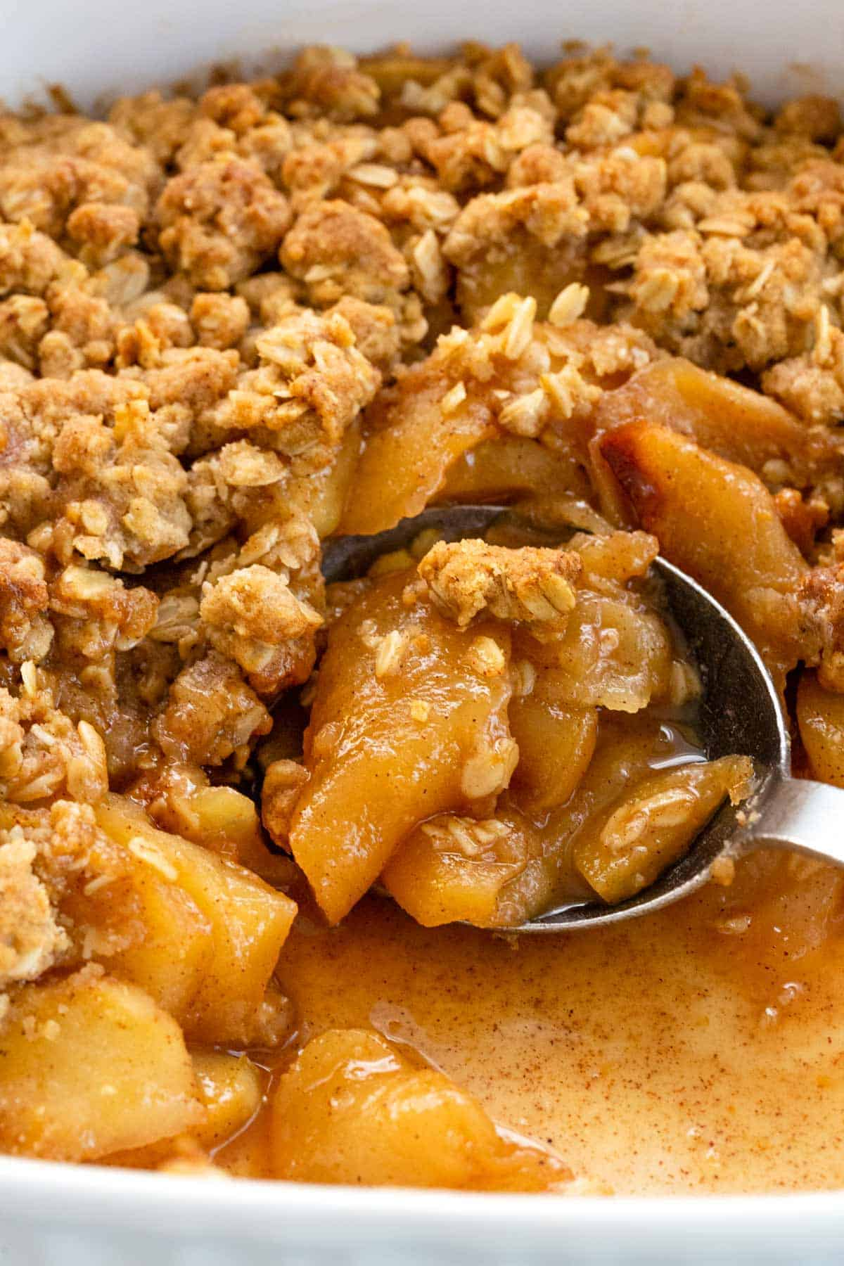 metal spoon scooping into an apple crisp