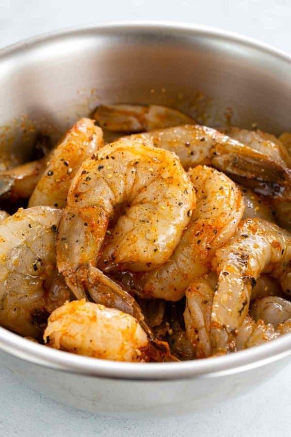 shrimp marinating in a silver mixing bowl