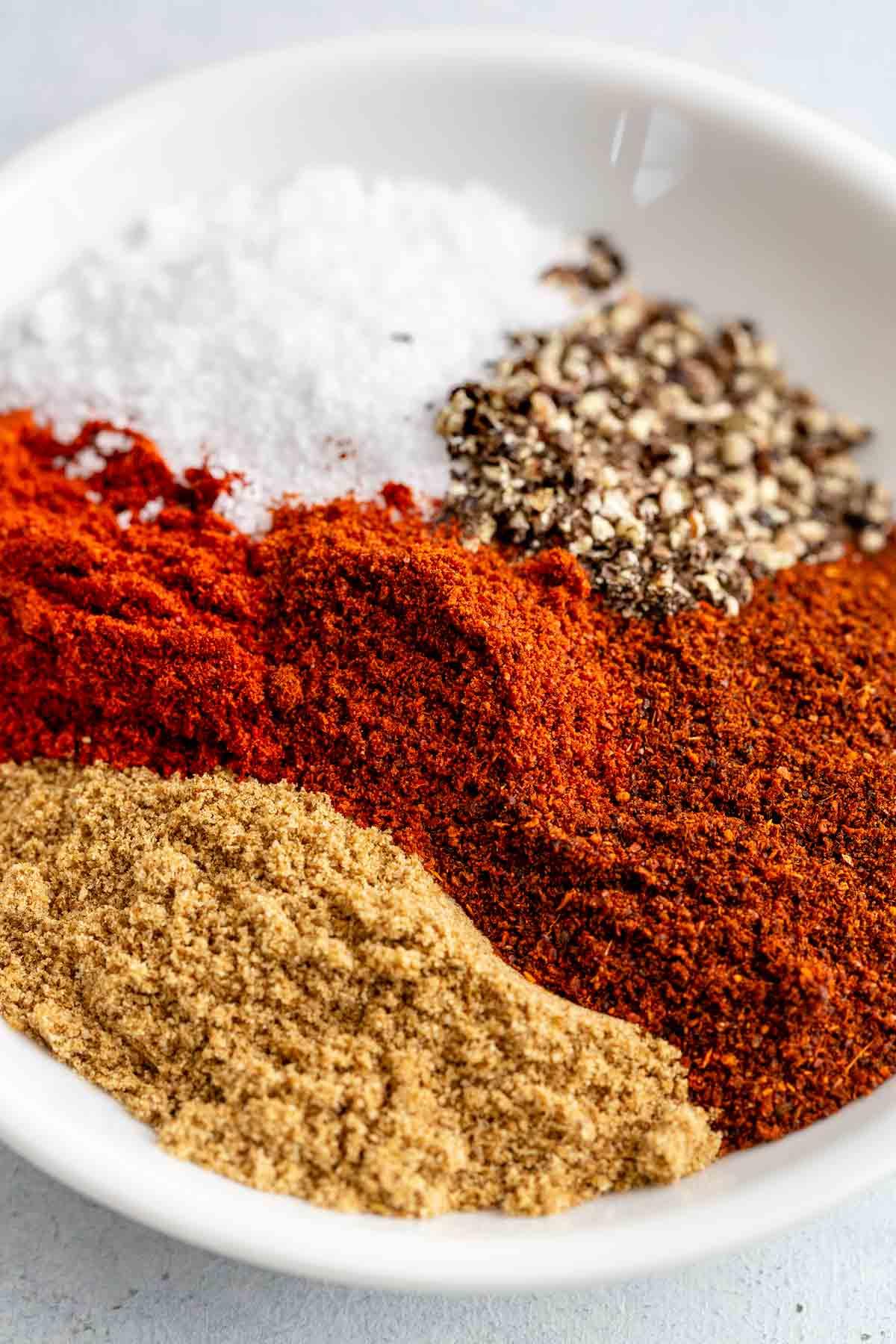 Bowl filled with chili powder, cumin, smoked paprika, chipotle chili powder, salt, and pepper