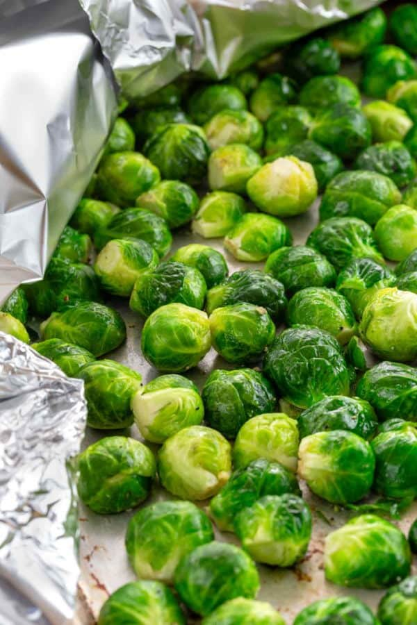 brussels sprouts steaming on a pan covered with aluminum foil