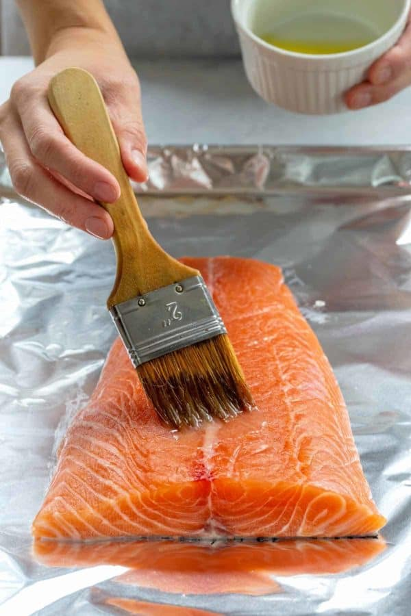 person brushing melted butter on top of a salmon fillet