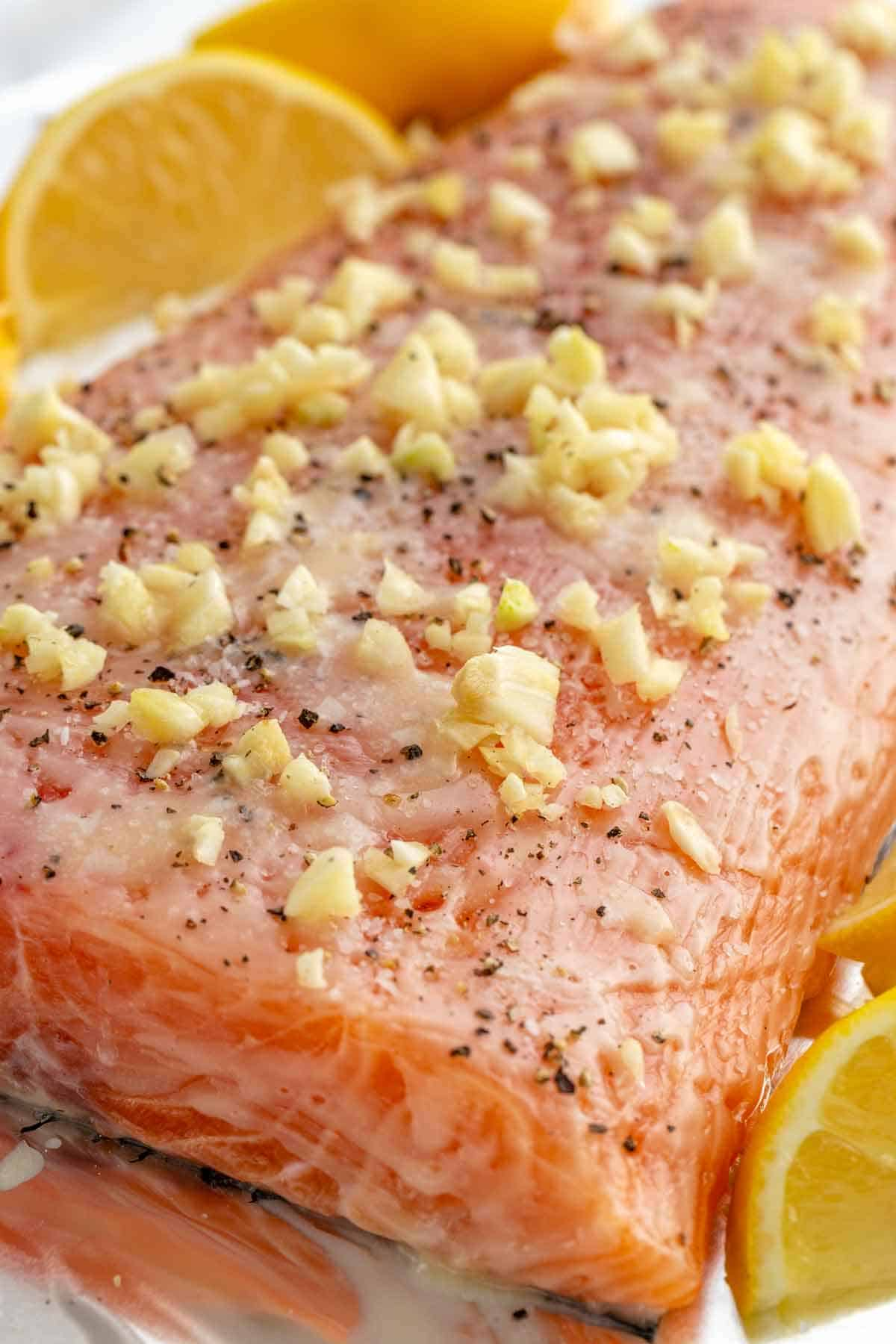 close up photo of crushed garlic pieces on top of a salmon fillet