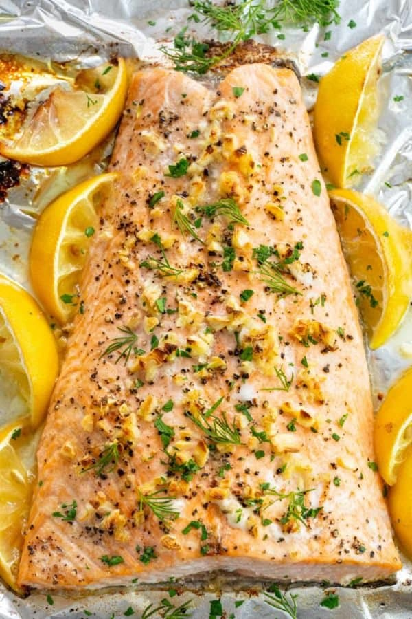 baked whole salmon fillet with lemon wedges on aluminum foil