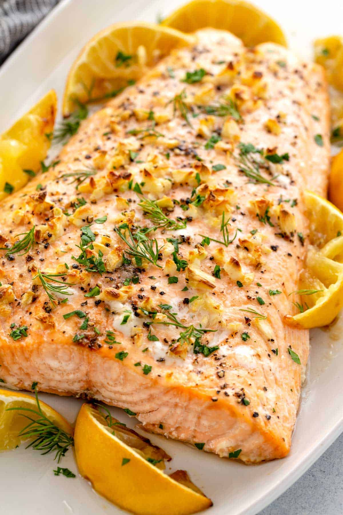 Baked salmon on a serving platter with roasted lemon wedges