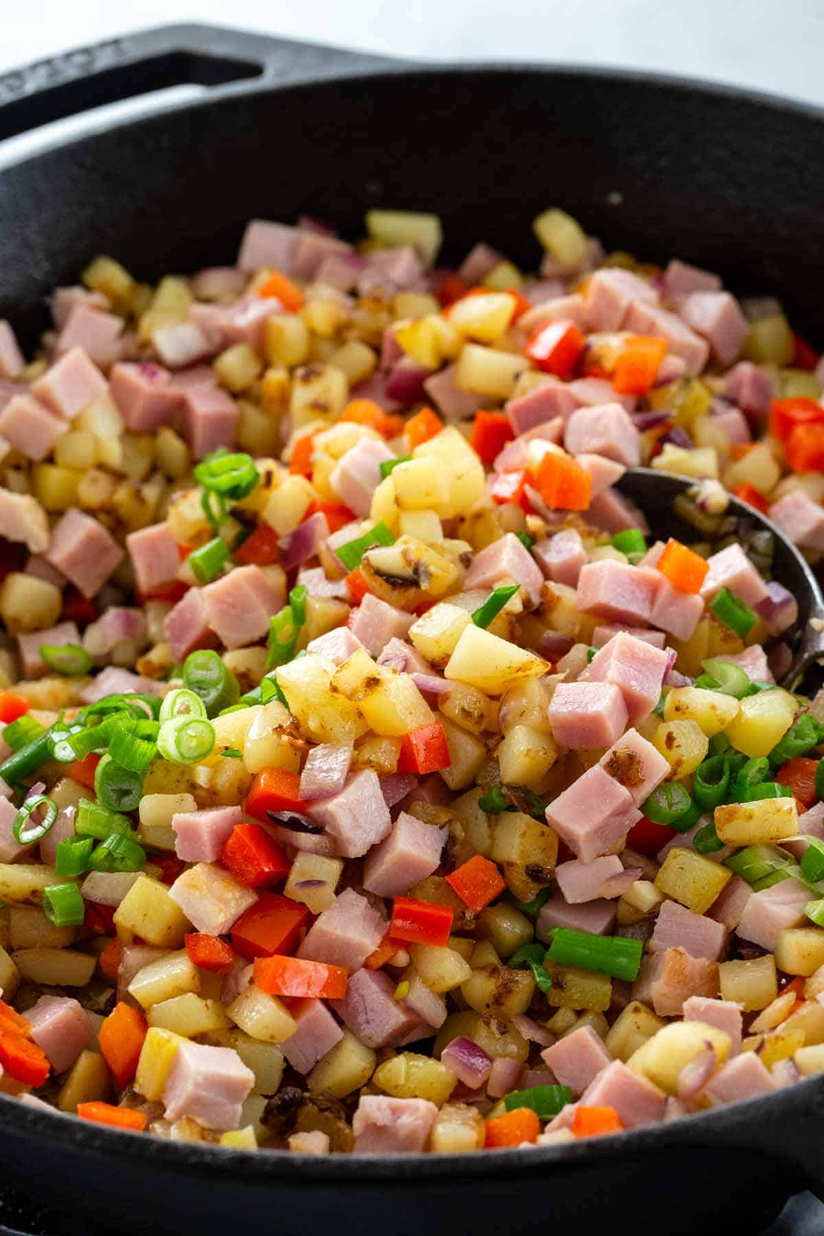 sautéing cubes of ham, potatoes, and peppers in a cast iron skillet