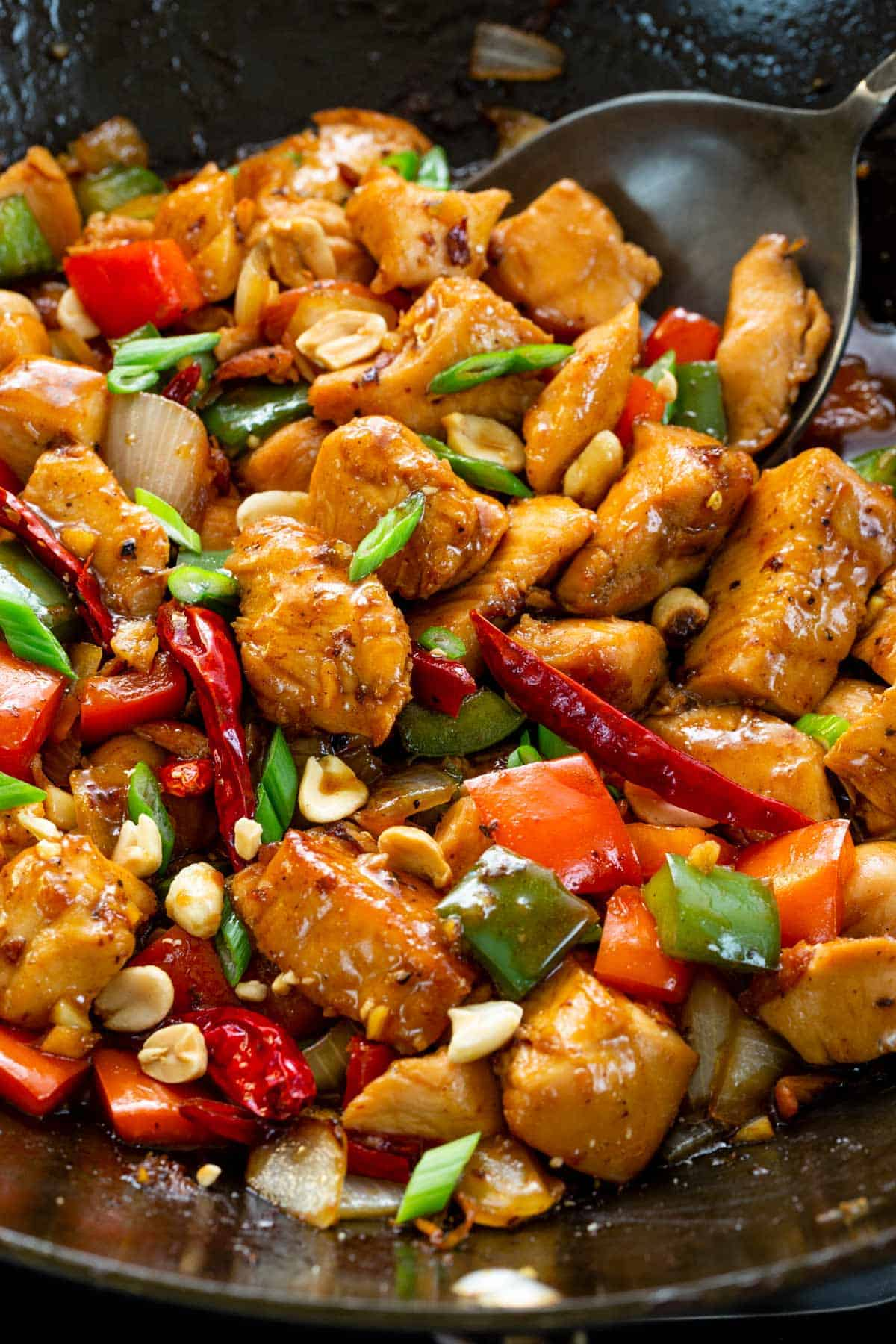 close up photo of kung pao chicken cooking in a wok