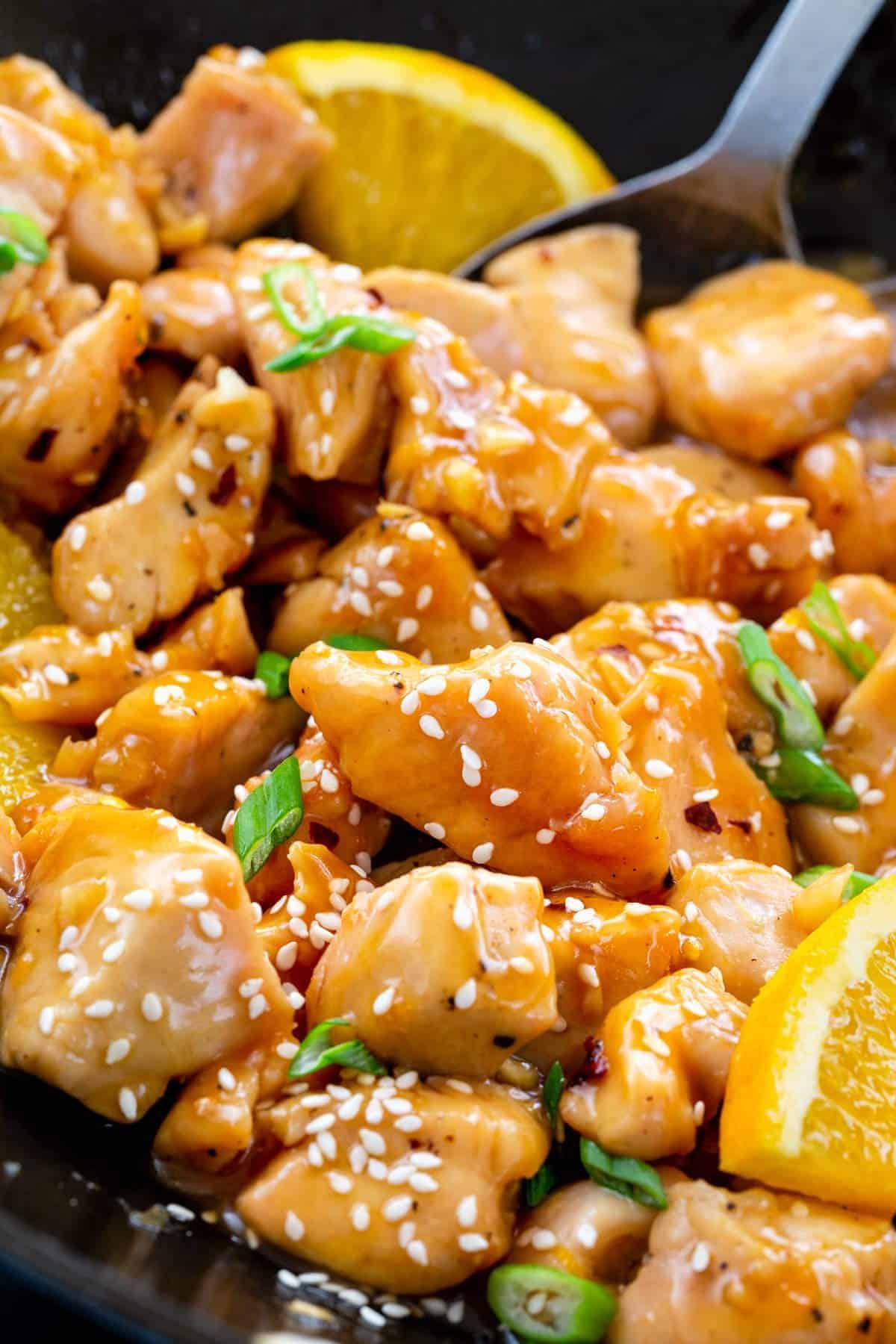 orange chicken cooking in a wok