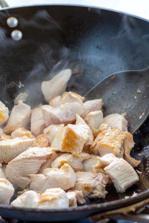 pieces of chicken cooking in a wok