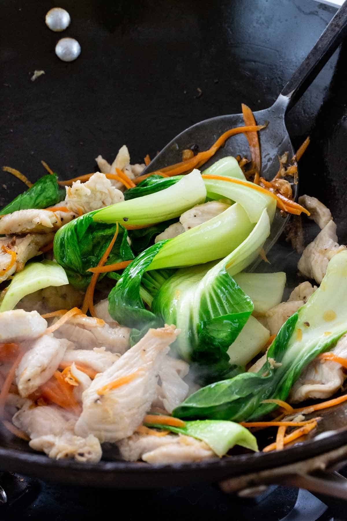 vegetables and chicken cooking in a wok