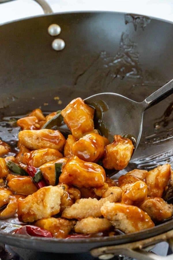 spatula stirring chicken and sauce inside a wok