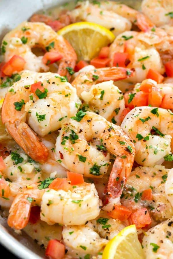 close up photo of shrimp scampi garnished with lemon wedges