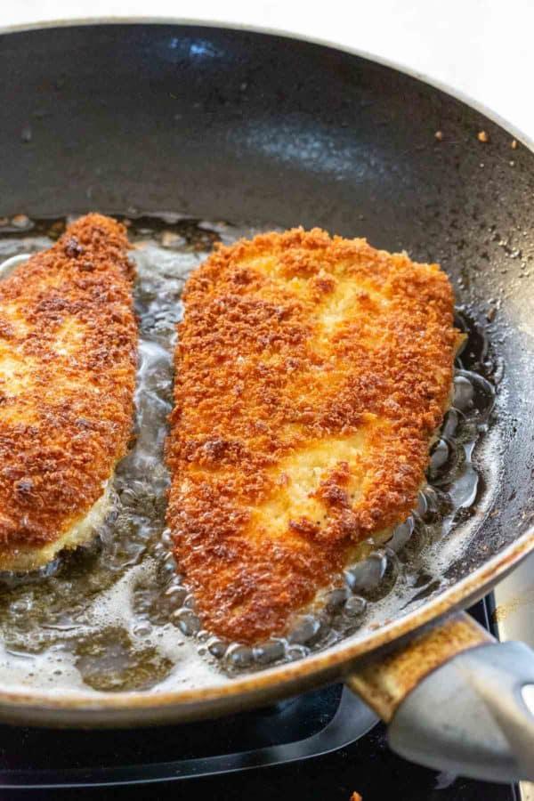 breaded chicken frying in a nonstick pan