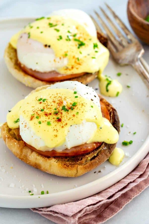 two servings of eggs benedict on a white plate