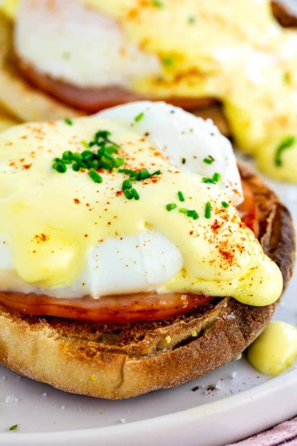 close up photo of eggs Benedict with hollandaise sauce on top