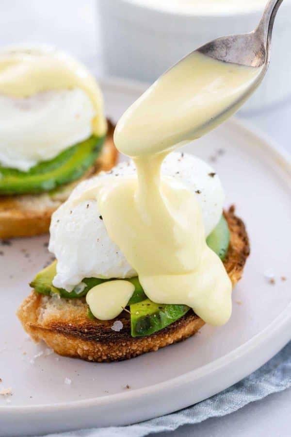 spoon pouring hollandaise sauce over a poached egg avocado toast