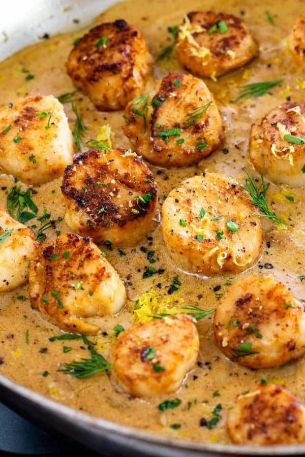 seared scallops in a pan with sauce and garnish