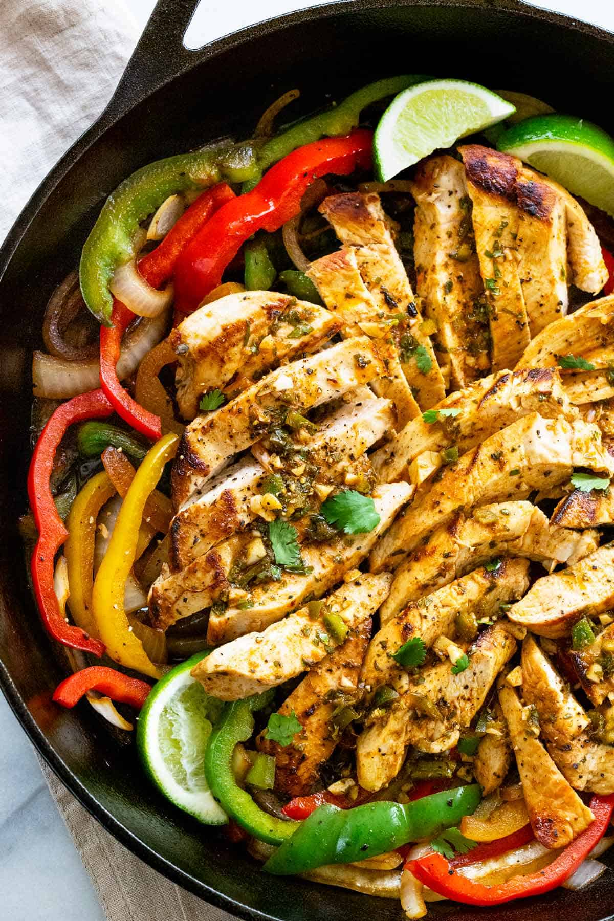 Easy chicken fajitas recipe with lean white meat infused with a cilantro lime marinade that\'s sauteed with crunchy bell peppers, and onions. #chickenfajitas #chickentacos #fajitas #mexicancuisine