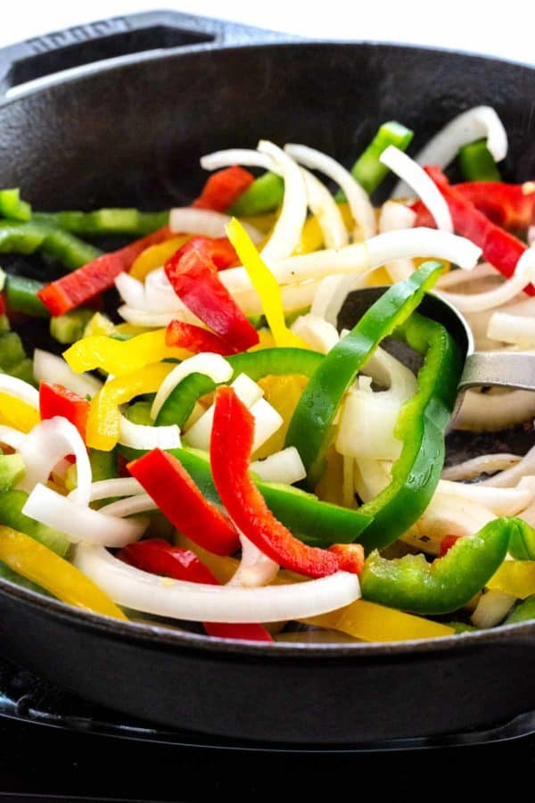 cooking sliced bell peppers and onions to make chicken fajitas