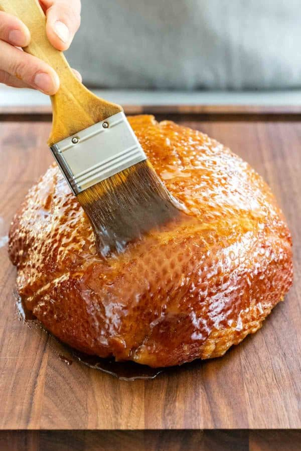basting brown sugar glaze on the outside of a ham