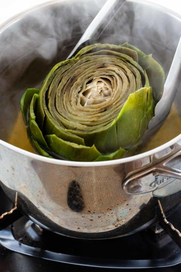 tongs removing a boiled artichoke from a pot of water