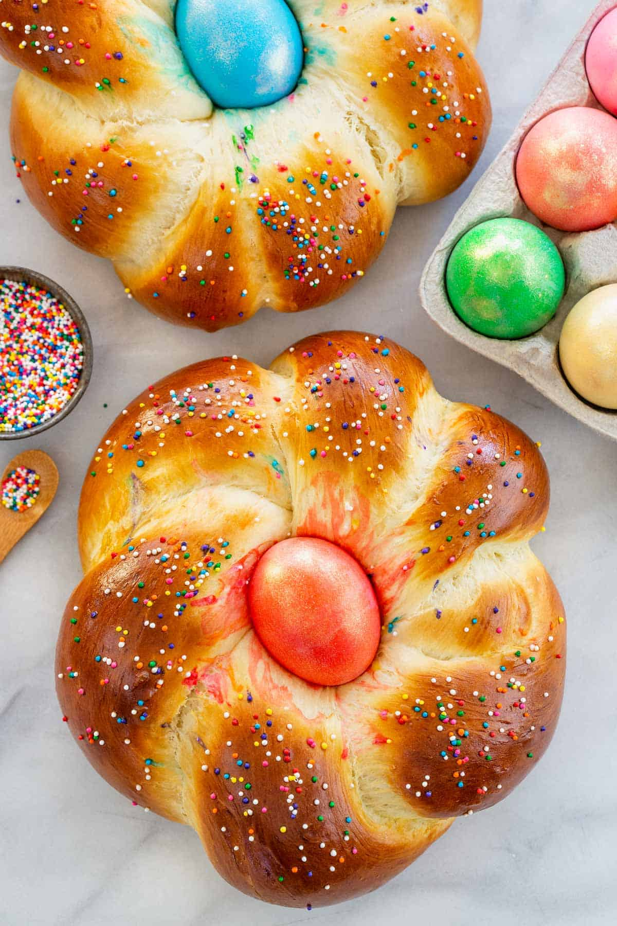 A traditional Italian Easter Bread recipe that's easy to make! A holiday bread with a colorful egg in the middle that\'s fun to decorate with family. #easterbread #italian #bread
