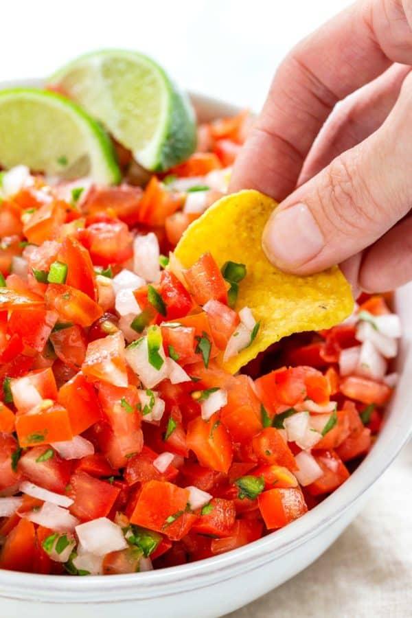 person dipping a chip into a bowl of pico de gallo