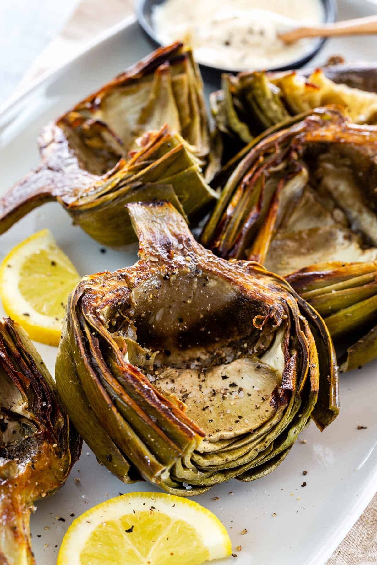 Roasted artichokes are a stunning appetizer! This technique develops deep caramelized flavors in the artichoke heart and the meaty leaves. #roastedartichokes #artichokes #appetizer #vegetarian