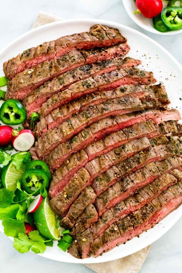 carne asada served family-style on a large white plate