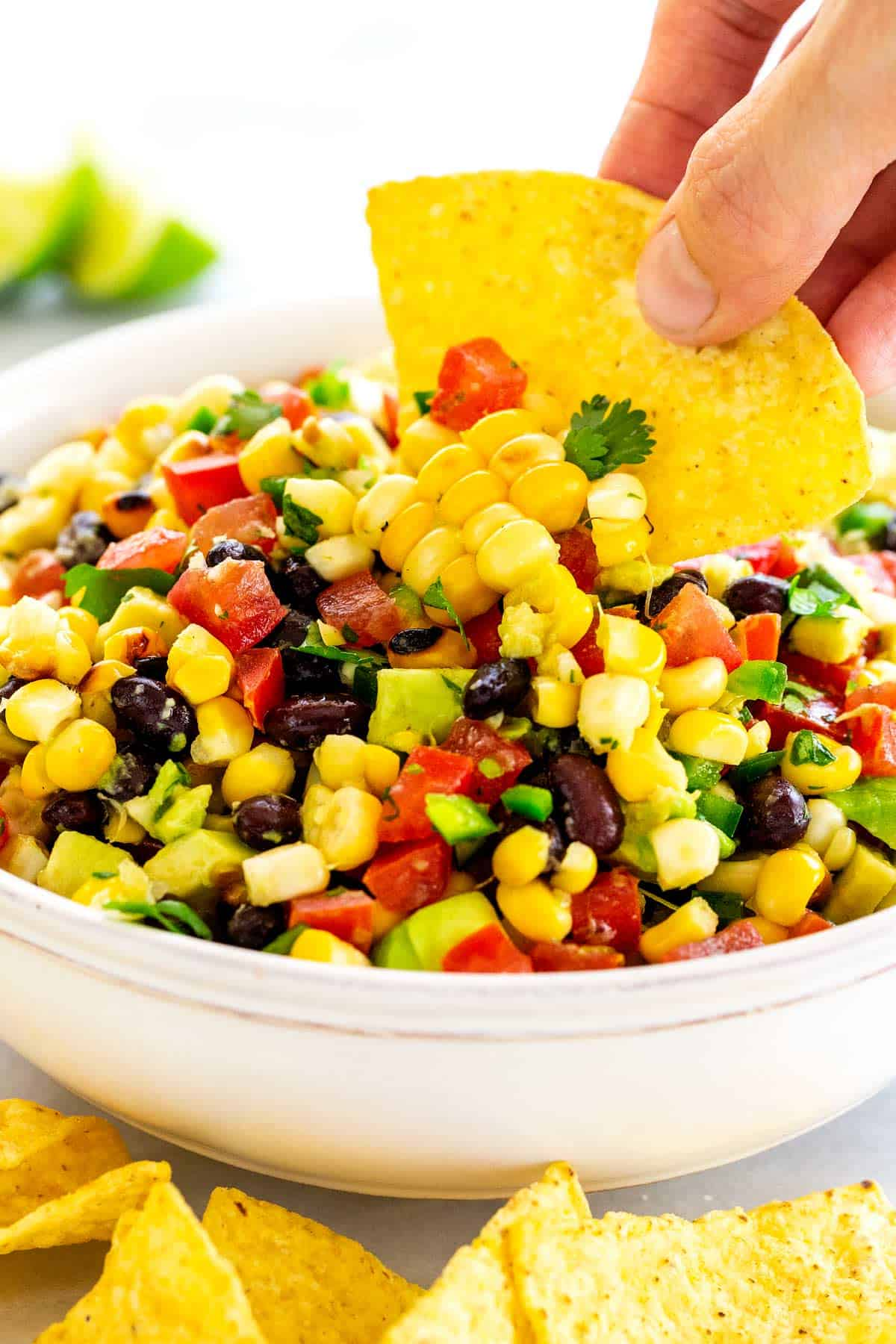 Easy corn salsa recipe with avocado and black beans. Made with either canned or grilled corn for an easy appetizer that goes perfect with tortilla chips. #cornsalsa #grilledcorn #salsa
