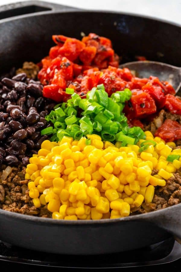 ground beef mixed with corn, beans, and tomatoes inside a skillet