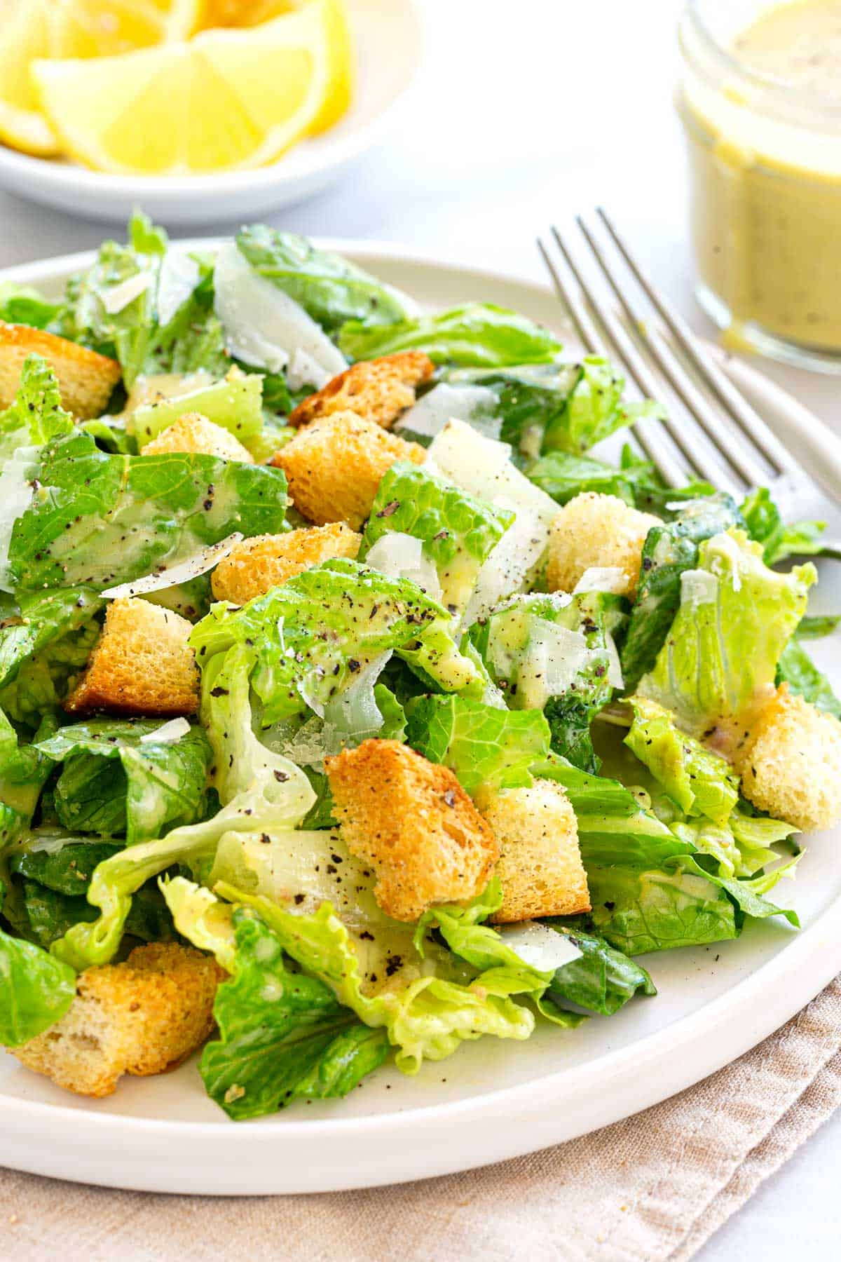 Classic caesar salad made with romaine lettuce and tossed with a creamy homemade dressing. Topped with aged Parmesan cheese and crunchy croutons. #caesarsalad #salad #anchovy