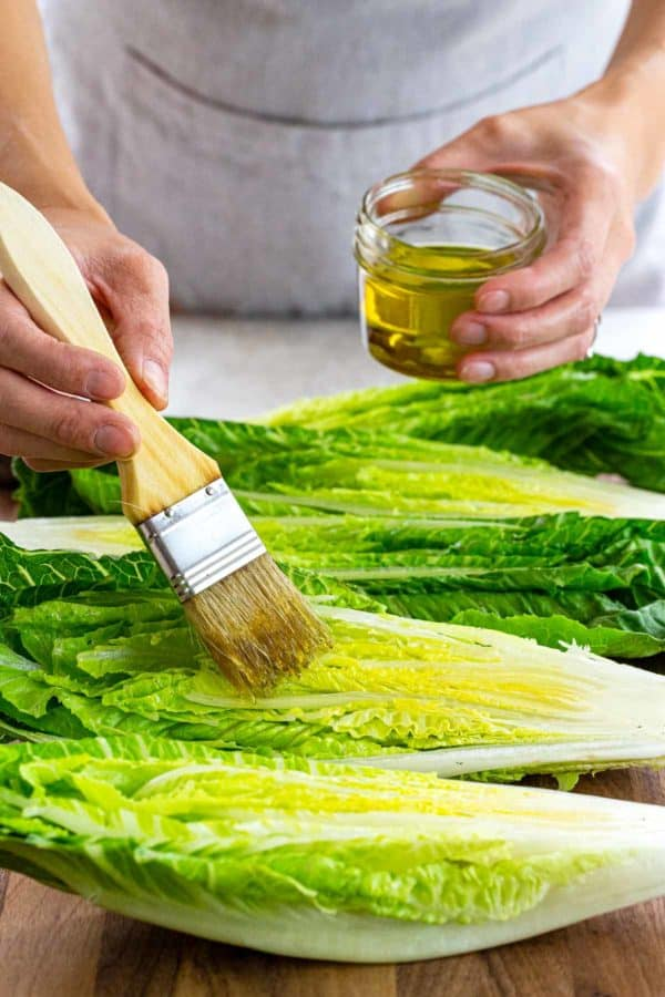 brushing olive oil on romaine lettuce