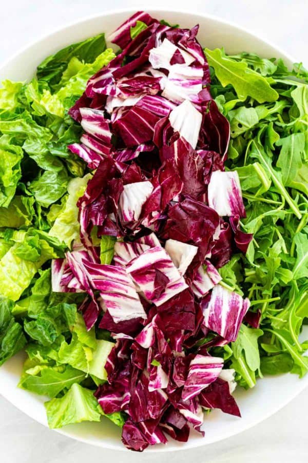 Chopped pieces of romaine and arugula in a bowl