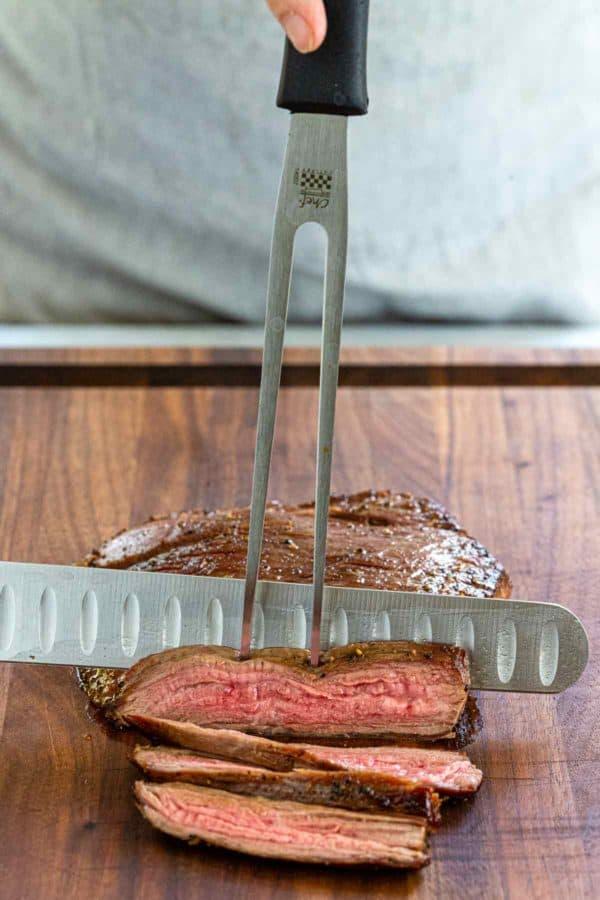 slicing steak on a wooden cutting board