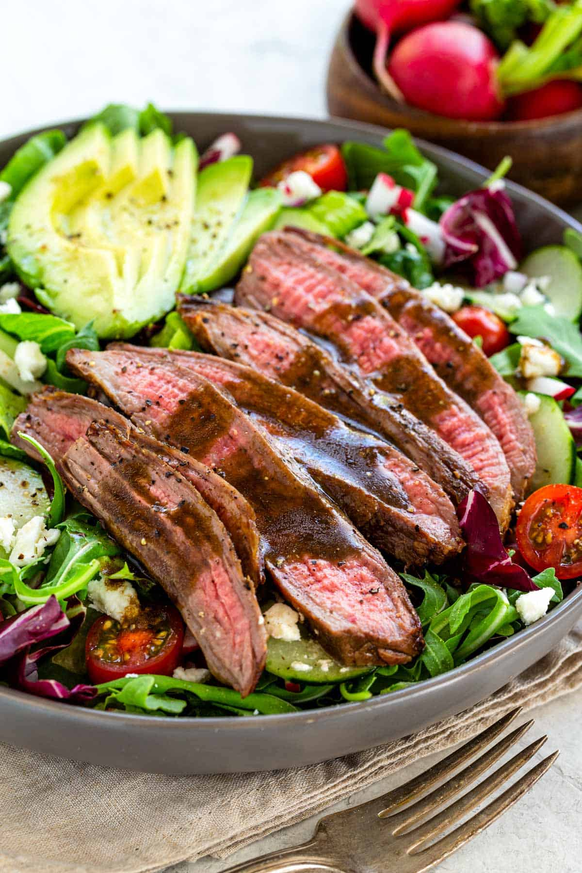 Steak salad with juicy slices of seasoned beef on a bed of colorful greens and crunchy vegetables. Mixed together with a homemade balsamic dressing. #steaksalad #lowcarb #entreesalad