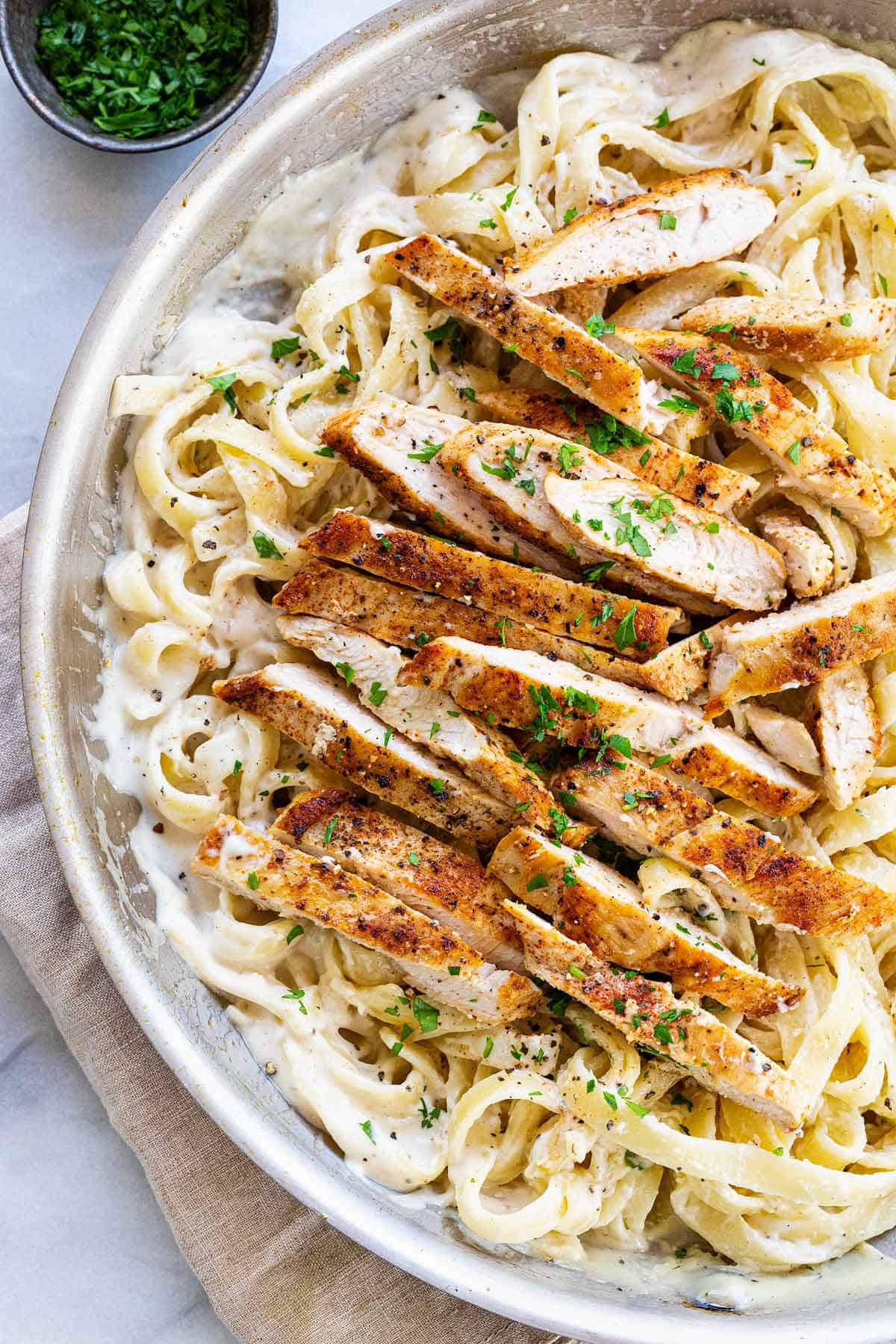 Chicken alfredo recipe with heavy cream, garlic, parmesan cheese, fettuccine noodles, and tender chicken breast for a classic Italian meal. #chickealfredo #italian #comfortfood