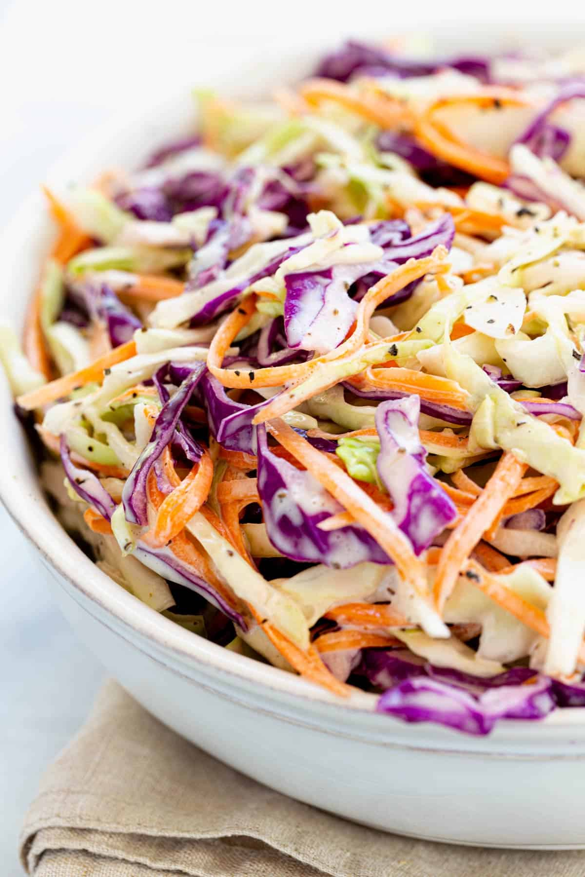 Easy homemade coleslaw recipe mixes crunchy shredded cabbage and carrots with a creamy dressing perfect for a side dish or sandwich topping. #coleslaw #cabbage #barbecue #potluck