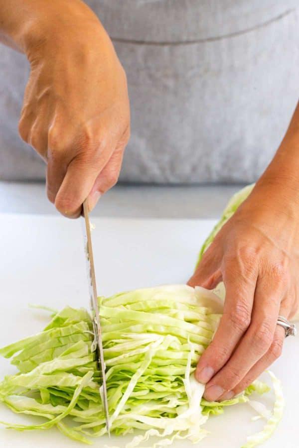 slicing cabbage into smaller pieces