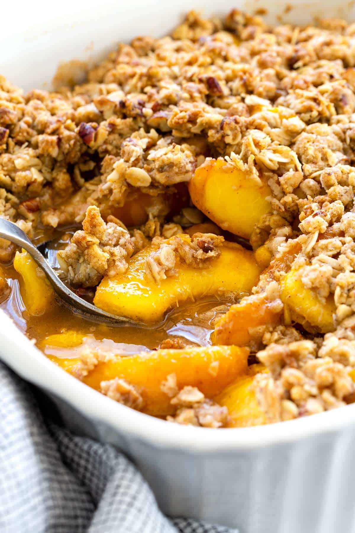 Peach crisp recipe made with fresh stone fruit and topped with a pecan-oat crumble. A delicious baked dessert using seasonal ingredients. #peachcrisp #peaches #dessert