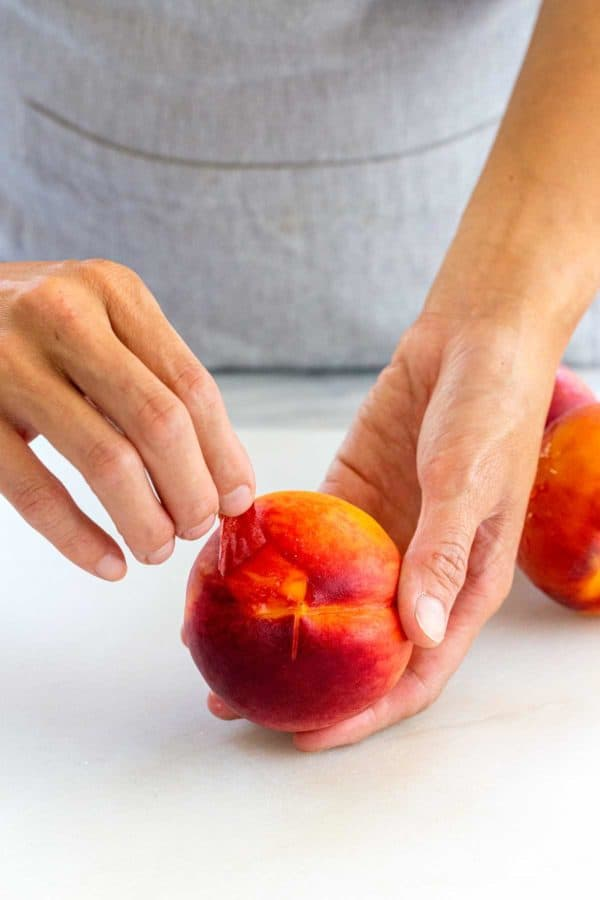 hands peeling the skin off of a peach