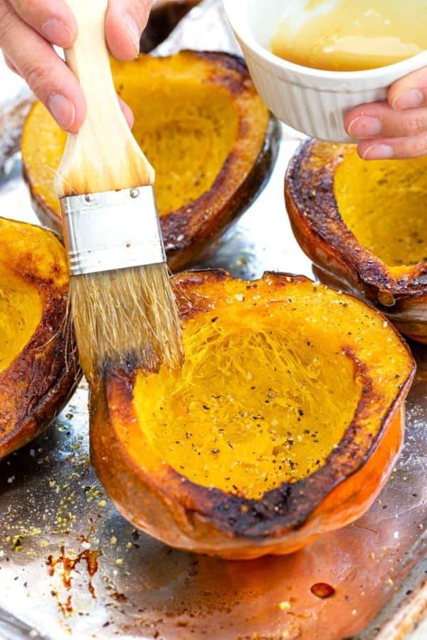 brushing maple syrup on acorn squash