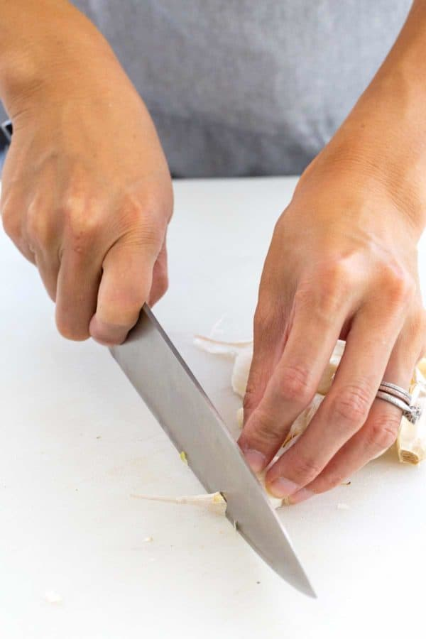 chef knife trimming the end off of a garlic clove